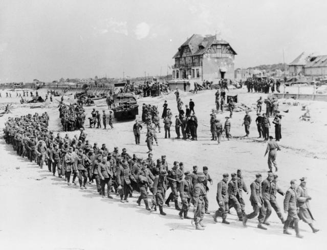 <p>German prisoners of war march along the Juno Beach landing area to a ship taking them to England after they were captured by Canadian troops at Bernières-sur-Mer, France, on June 6, 1944. (Photo: Ken Bell/National Archives of Canada/handout via Reuters) </p>