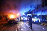 <p>A demonstrator gestures near a burning police vehicle during a protest against a new proposed policing bill, in Bristol, Britain, March 21, 2021. REUTERS/Peter Cziborra</p>
