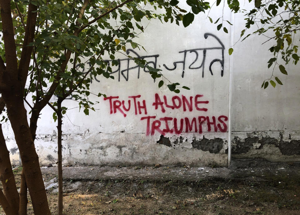 In this Wednesday, Dec. 18, 2019 photo, a graffiti covers the wall of a building at Jamia Millia Islamia University in New Delhi, India. Students of this New Delhi university have turned the campus' sandstone walls into a canvas of discontent. The spray-painted slogans and symbols reflect their opposition to a new law that provides a path to citizenship for religious groups from neighboring countries except Muslims. (AP Photo/Sheikh Saaliq)