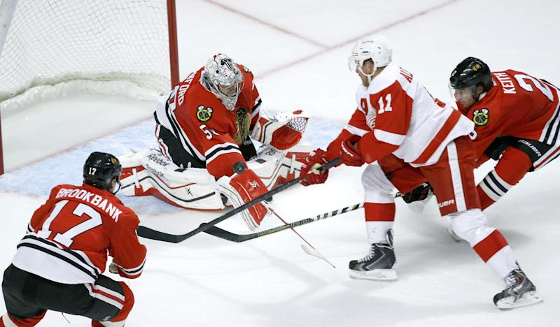 Chicago Blackhawks goalie Corey Crawford (50) makes a save on a shot by Detroit Red Wings right wing Daniel Alfredsson (11) as defenseman Sheldon Brookbank (17) and defenseman Duncan Keith also defend during the second period of an NHL preseason hockey game Tuesday, Sept. 17, 2013, in Chicago. (AP Photo/Charles Rex Arbogast)