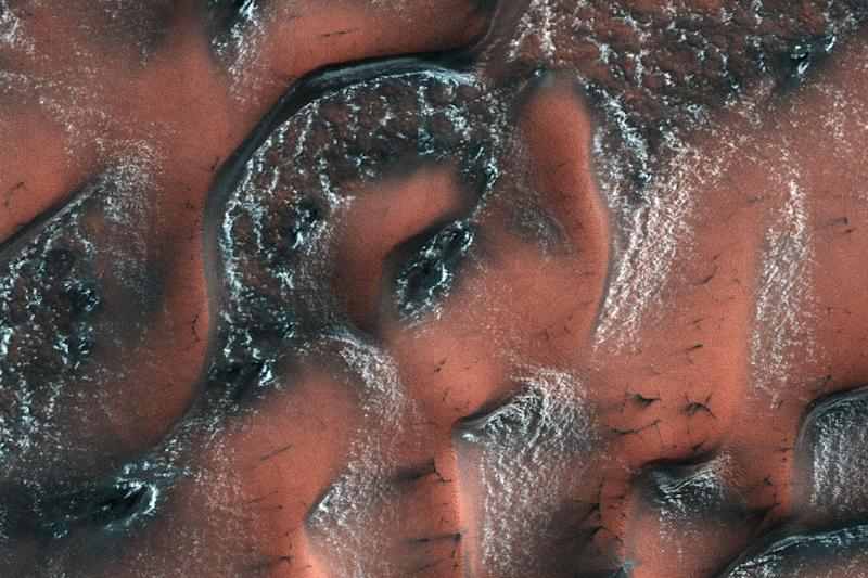 By the 2030s, NASA hopes to send human explorers to Mars, the surface of which is seen in a May 2017 handout photo covered in carbon dioxide snow and ice, different from the buried glaciers researchers have spotted