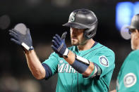 Seattle Mariners' Tom Murphy directs applause toward his dugout after hitting a one-run single against the Kansas City Royals in the second inning of a baseball game Friday, Aug. 27, 2021, in Seattle. (AP Photo/Elaine Thompson)