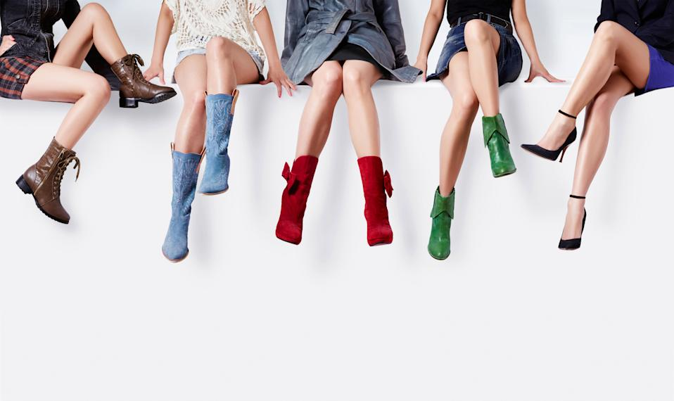 Many woman with different colorful shoes and boots sitting together against the white wall. Copy space under the shoes.