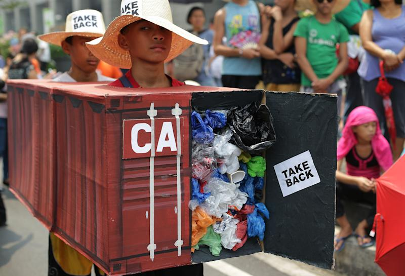 "Filipino environmental activists wear a mock container vans filled with garbage to symbolize the 50 containers of waste that were shipped from Canada to the Philippines two years ago, as they hold a protest outside the Canadian embassy at the financial district of Makati, south of Manila, Philippines on Thursday, May 7, 2015. The group held the protest to assert that the country is not a waste dumping and burning zone and to call on Philippine President Benigno Aquino III to talk about the said ""illegal"" waste issue when he meets Canadian Prime Minister Stephen Harper during his state visit on May 7.(AP Photo/Aaron Favila)"