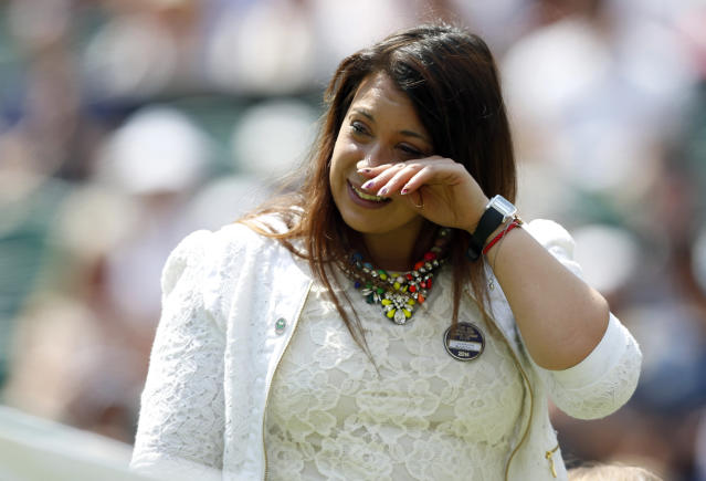 2013 Wimbledon champion Marion Bartoli of France wipes her eyes as she arrives on court to take part in the coin toss for the match between Julia Glushko of Israel and Sabine Lisicki of Germany at the All England Lawn Tennis Championships in Wimbledon, London, Tuesday, June 24, 2014. Traditionally the reigning champion would play her first match on Centre Court but due to Bartoli's retirement the runner up Lisicki will open play. (AP Photo/Sang Tan)