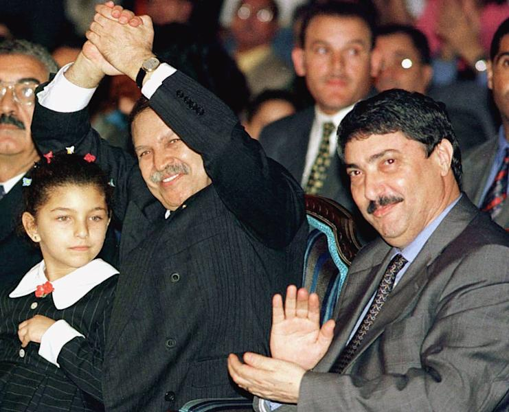FILE - This file photo dated 1999 shows Algerian President Abdelaziz Bouteflika, left, waving next to his adviser Ali Benflis during meeting in Algiers, Algeria. Unidentifed girl at left. The Algerian government announced Friday, Jan. 17, 2014 the official date of its presidential elections, yet with just 90 days to go before one of the most important votes in its history, it is not yet clear who is even running. The presidential elections, now scheduled for April 17, could possibly see the handing over of power to a new generation and for the first time Algeria would be led by someone who didn't fight in the 1958-1962 war for independence against France. (AP Photo, File)