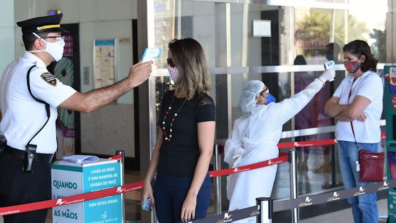 Workers check the body temperature of people before entering a shopping mall in Brasilia, Brazil, on May 27, 2020,