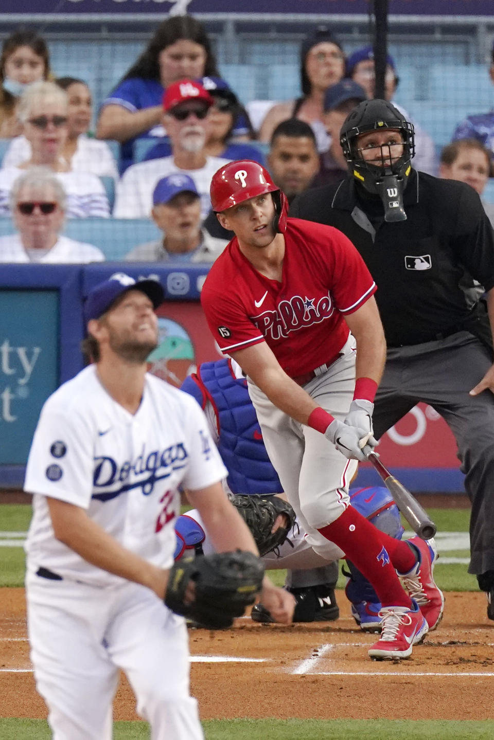 Philadelphia Phillies' Rhys Hoskins, center, hits a solo home run as Los Angeles Dodgers starting pitcher Clayton Kershaw, left, watches along with umpire Manny Gonzalez during the first inning of a baseball game Wednesday, June 16, 2021, in Los Angeles. (AP Photo/Mark J. Terrill)