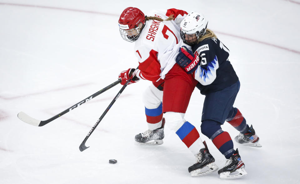Russia's Kristi Shashkina, left, passes the puck as she is is checked by Savannah Harmon, of the United States, during the second period of a match at the International Ice Hockey Federation (IIHF) Women's World Championships in Calgary, Alberta, Tuesday, Aug. 24, 2021. (Jeff McIntosh/The Canadian Press via AP)