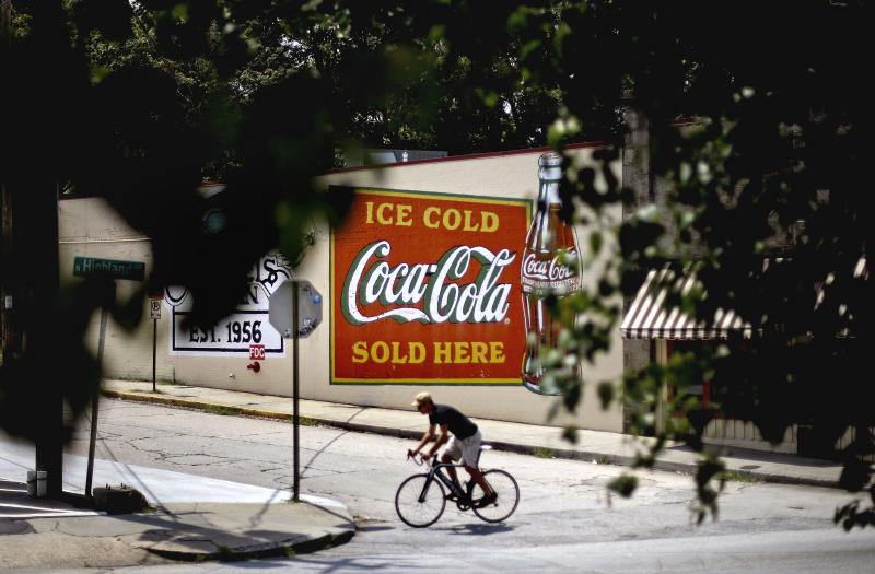 In this Monday, July 16, 2012, photo, a bicyclist passes in front of a billboard for Coca Cola outside a restaurant in Atlanta. The Coca-Cola Co. says its net income slipped in the second quarter from a year ago, as rising costs for ingredients offset its expansion overseas. The world's biggest beverage maker, which makes Minute Maid, Powerade and Dasani, says revenue growth was powered by higher prices in the U.S. and expansion in emerging markets such as India, where volume rose 20 percent. (AP Photo/David Goldman)