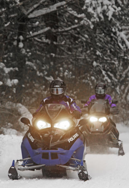 Snowmobiles travel a newly-groomed trail on Monday, Dec. 31, 2012 in East Montpelier, Vt. The big snow is giving a big boost to snowmobilers across Vermont, New Hampshire and Maine. Parts of the region have received two feet of snow and more over the last several days, giving a boost to the sport that was hampered last season by a near-snowless winter. (AP Photo/Toby Talbot)