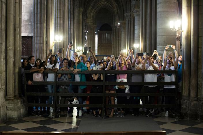 <p>Tourists take pictures of First Lady Melania Trump and French president's wife Brigitte Macron visiting Notre Dame Cathedral in Paris, Thursday, July 13, 2017. (Photo: Kamil Zihnioglu/AP) </p>