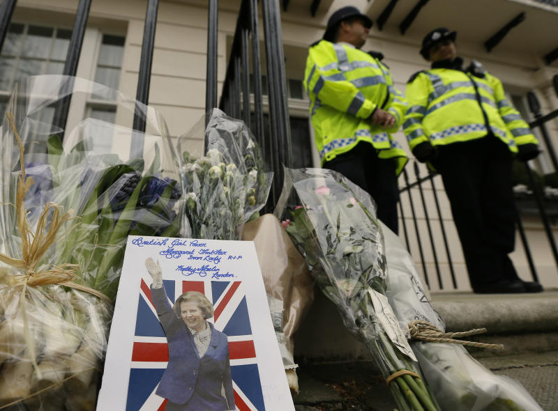 """A card is left on a floral tribute outside former British Prime Minister Baroness Thatcher's home in London, Tuesday, April 9, 2013. Margaret Thatcher, the combative """"Iron Lady"""" who infuriated European allies, found a fellow believer in former US President Ronald Reagan and transformed her country by a ruthless dedication to free markets in 11 bruising years as prime minister, died Monday, April 8, 2013. She was 87 years old. (AP Photo/Kirsty Wigglesworth)"""