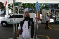 A worker of National Petroleum Agency ANP, makes a procedure to check fuel quality at a gas station in Rio de Janeiro