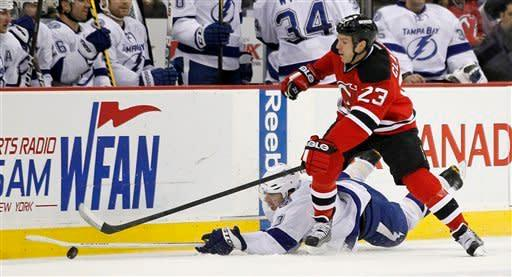 Tampa Bay Lightning's Brett Clark, bottom, goes down while competing for the puck with New Jersey Devils' David Clarkson in the second period of an NHL hockey game, Thursday, March 29, 2012, in Newark, N.J. (AP Photo/Julio Cortez)