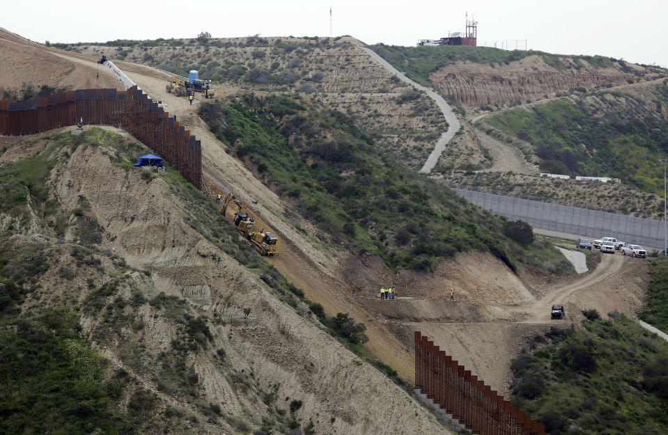 FILE - In this March 11, 2019, file photo, construction crews replace a section of the primary wall separating San Diego, above right, and Tijuana, Mexico, below left, seen from Tijuana, Mexico. The Biden administration says it will begin work to address flooding and soil erosion risks from the unfinished wall on the U.S. border with Mexico. It also began providing answers on how it will use unspent money from shutting down one of President Donald Trump's signature domestic projects. The Defense Department says it will use unobligated money for military construction projects for its initial purpose. The repair work will take place in Texas' Rio Grande Valley and San Diego. (AP Photo/Gregory Bull, File)