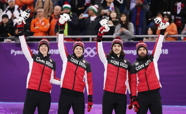 Bronze medalists Samuel Girard, Charles Hamelin, Charle Cournoyer and Pascal Dion of Canada celebrate during the victory ceremony of the 5,000-metre relay.