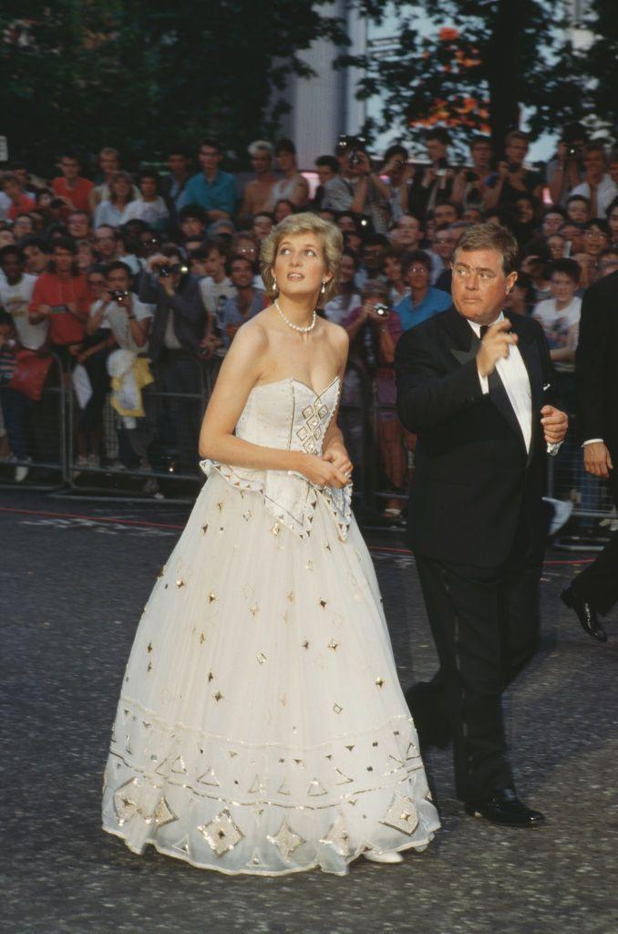 """<p>Princess Diana and Prince Charles (not pictured) both attended the premiere of <em>The Living Daylights</em>. Diana's dress here, which she wore multiple times, is likely the inspiration for Kristen Stewart's gown on the <a href=""""https://www.townandcountrymag.com/leisure/arts-and-culture/a32894233/princess-diana-movie-spencer-news/"""" rel=""""nofollow noopener"""" target=""""_blank"""" data-ylk=""""slk:poster for the movie, Spencer"""" class=""""link rapid-noclick-resp"""">poster for the movie, <em>Spencer</em></a>. </p>"""