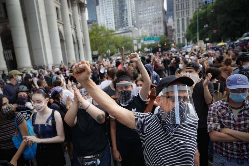 Protesters block traffic as they gather at an encampment outside City Hall, Tuesday, June 30, 2020, in New York. New York City lawmakers are holding a high-stakes debate on the city budget as activists demand a $1 billion shift from policing to social services and the city grapples with multibillion-dollar losses because of the coronavirus pandemic. (AP Photo/John Minchillo)