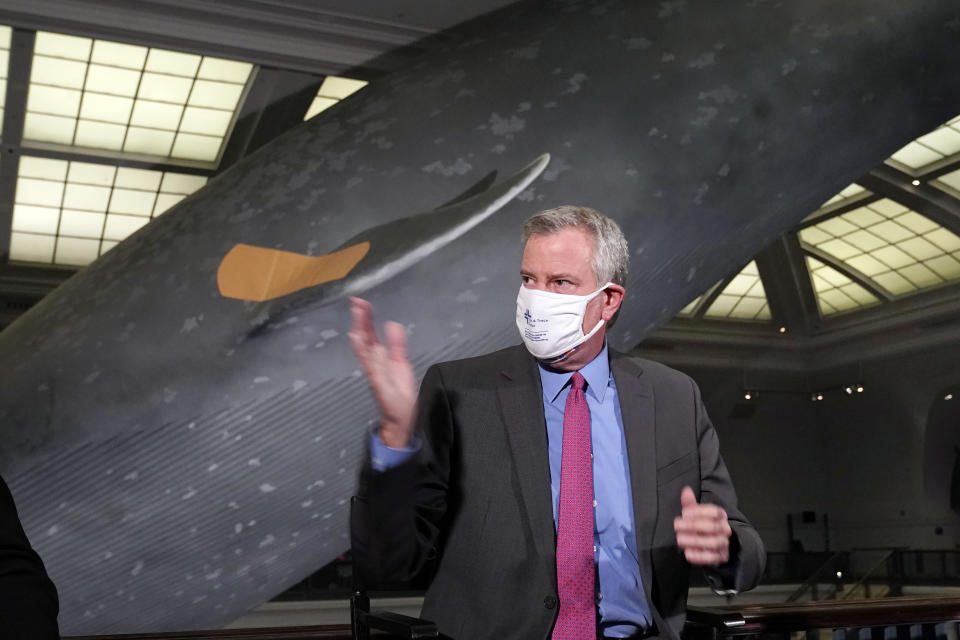 New York Mayor Bill de Blasio gestures as he sits in front of the 94-foot-long, 21,000-pound model of a blue whale, wearing a bandage, at COVID-19 vaccination site in the Milstein Family Hall of Ocean Life, at the American Museum of Natural History, in New York, Friday, April 23, 2021. (AP Photo/Richard Drew)