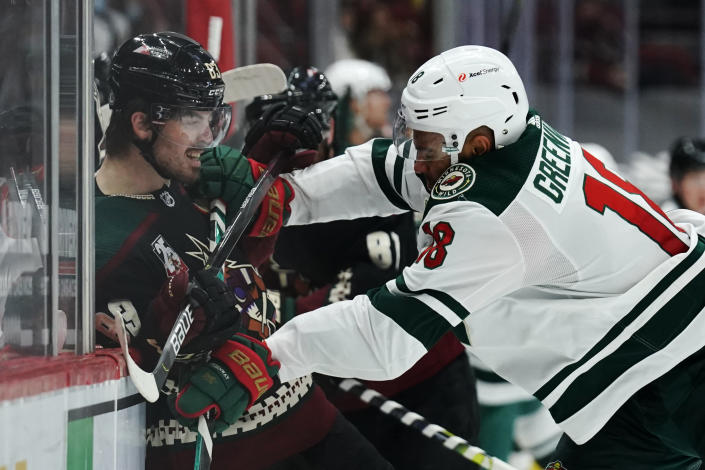 Minnesota Wild left wing Jordan Greenway (18) checks Arizona Coyotes right wing Conor Garland during the second period of an NHL hockey game, Friday, March 5, 2021, in Glendale, Ariz. (AP Photo/Rick Scuteri)