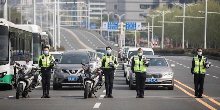Police officers in Wuhan stand in silence as traffic stops during a three-minute silence to coronavirus victims on April 4, 2020.