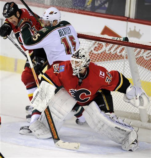 Minnesota Wild's' Dany Heatley, centre, battles in the crease with Calgary Flames' Olli Jokinen, left, from Finland, as Calgary goalie Miikka Kiprusoff, from Finland, follows the puck during third period NHL action in Calgary, Alberta, Tuesday Dec. 20, 2011. (AP Photo/The Canadian Press, Larry MacDougal)