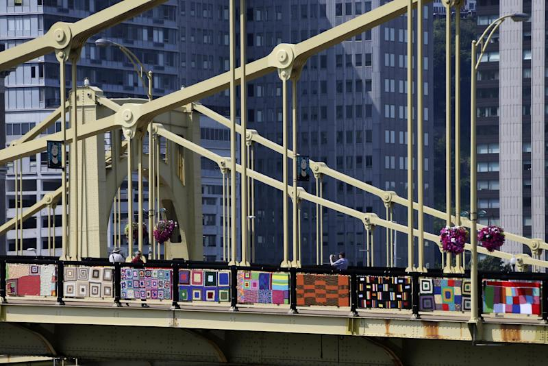 Pedestrians walk across the Andy Warhol bridge on Monday, Aug. 12, 2013 in downtown Pittsburgh. More that 1,800 knitters have covered the bridge in 3,000 feet of colorful yarn. Volunteers worked all weekend to attach 580 blanket-sized, hand- knitted panels to the pedestrian walkways. Organizers say it is the nation's largest yarn bomb. (AP Photo/Gene J. Puskar)