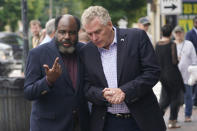 Democratic gubernatorial candidate, former Gov. Terry McAuliffe, right, talks with former Delegate Fenton Bland, during a tour of downtown Petersburg, Va., Saturday, May 29, 2021. McAuliffe faces four other Democrats in the a primary June 8. (AP Photo/Steve Helber)