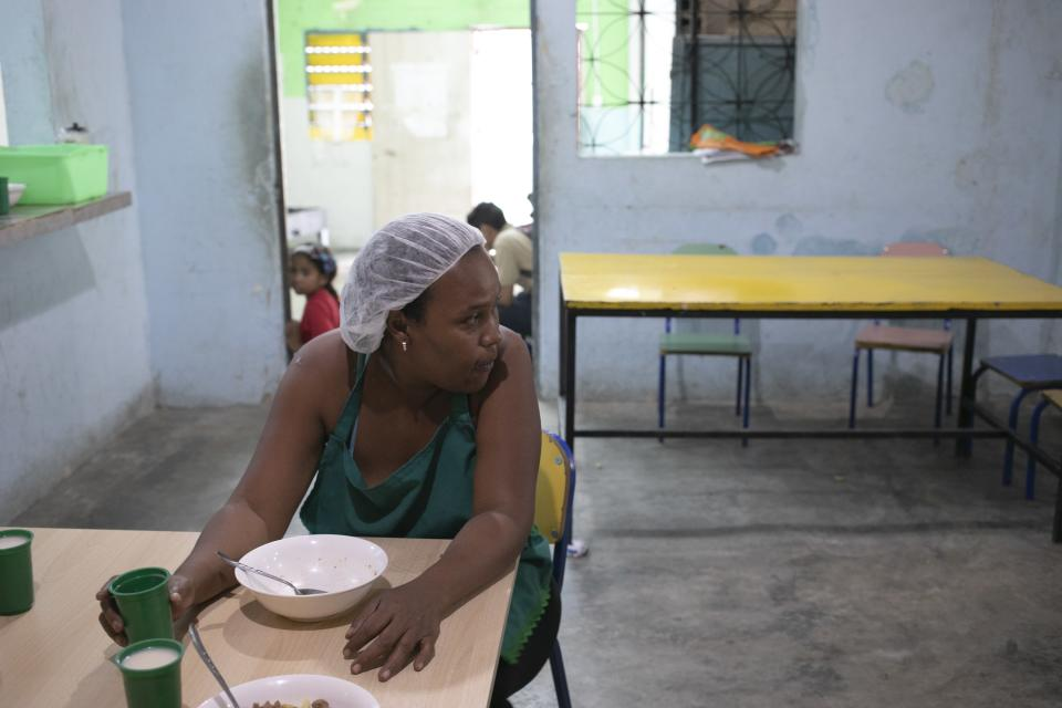 In this Feb. 27, 2020 photo, Yeri Guerra, 39, sits inside a soup kitchen in the Petare slum, in Caracas, Venezuela. Guerra has volunteered at a neighborhood soup kitchen run by a charity, where she and her two sons eat lunch five days a week. She often saves some of her lunch to eat as dinner. (AP Photo/Ariana Cubillos)