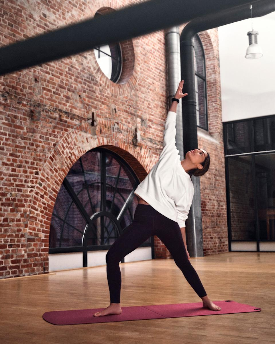 """<p>Montblanc Summit Lite. A woman wearing the Summit Lite on her wrist stands in a """"peaceful warrior' pose on a red yoga mat in a loft.</p>"""
