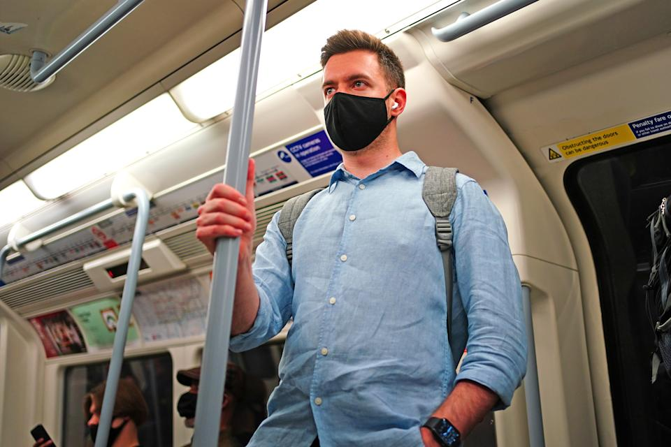 A man wearing a facemask on an underground tube train in central London, during the easing of lockdown restrictions in England. Picture date: Sunday July 4, 2021.