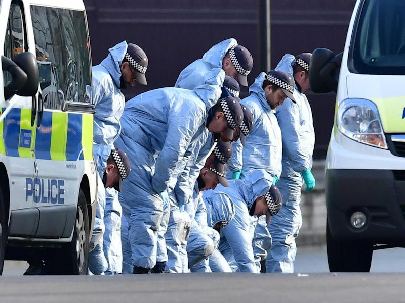 Police conduct a fingertip search near Parliament yesterday (PA)