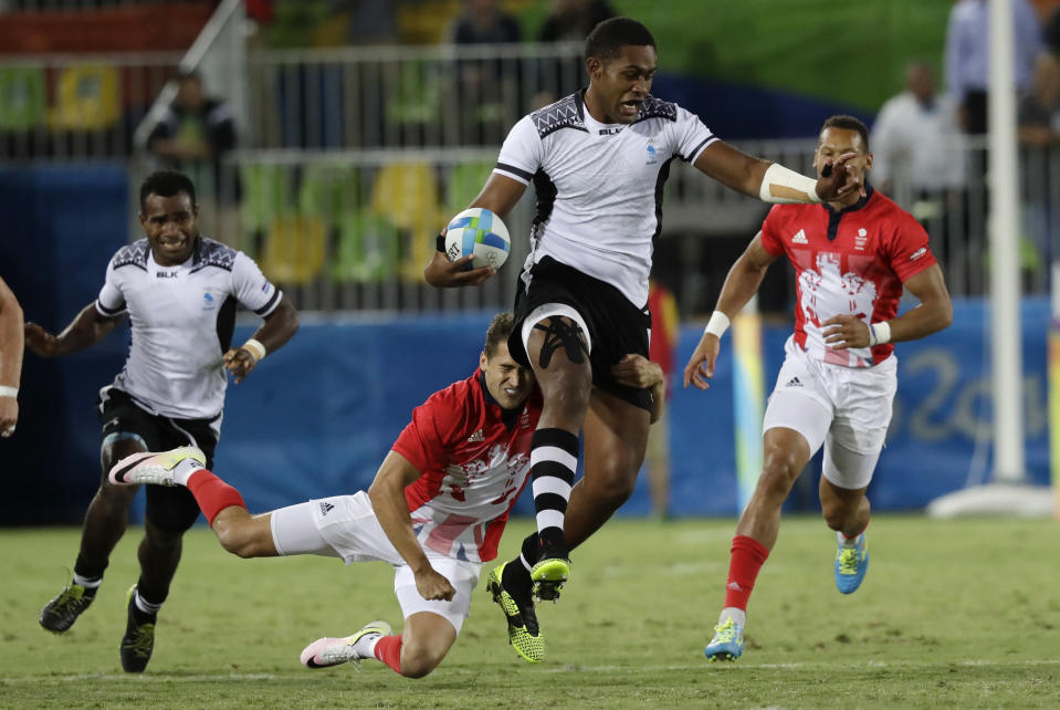FILE - In this Aug. 11, 2016, file photo, Viliame Mata of Fiji evades a tackle during the gold medal mens rugby sevens match against Britain at the 2016 Summer Olympics in Rio de Janeiro, Brazil. It was rugby in fast forward and it generated millions of new fans across the world. Rugby sevens made its Olympic debut in Rio de Janeiro in 2016 bringing all the usual hard-hitting tackles, collisions and swerving runs but leaving out the slow-mo elements of the traditional 15-a-side game. (AP Photo/Robert F. Bukaty, File)