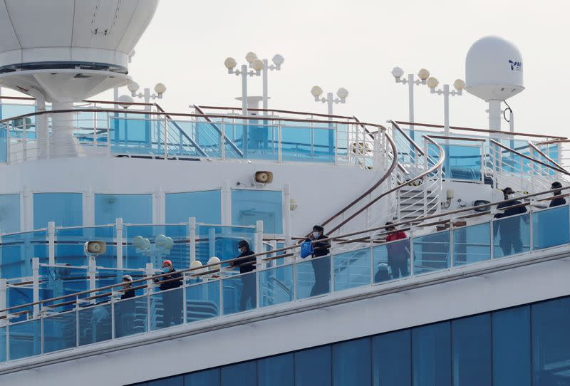 Passengers look out from a deck of the cruise ship Diamond Princess at Daikoku Pier Cruise Terminal in Yokohama, south of Tokyo, Japan