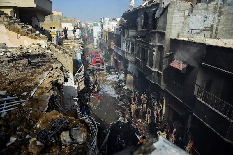 Rescue workers gather at the site after a Pakistan International Airlines aircraft crashed in a residential area in Karachi (AFP via Getty Images)