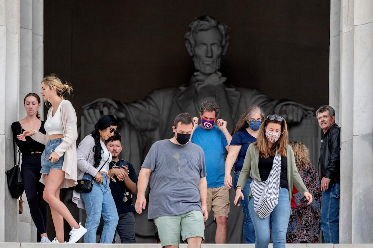 Tourists, some in face masks while others are not, visit the Lincoln Memorial in Washington, DC, on May 14, 2021. (Jim Watson/AFP via Getty Images)