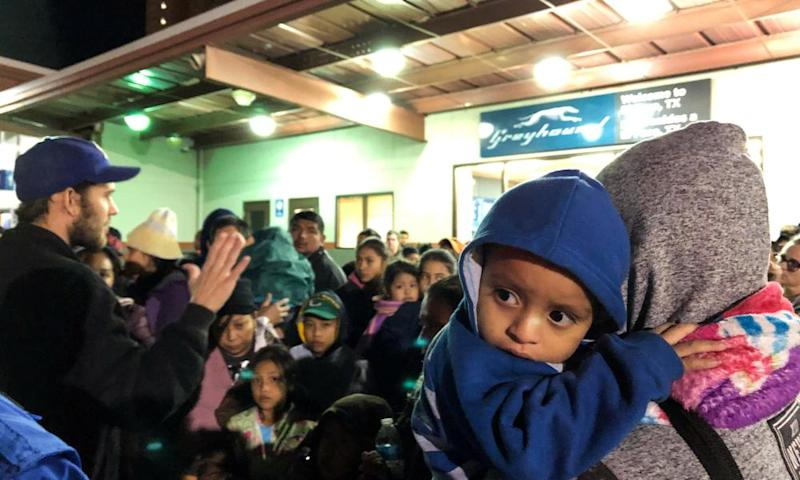 Some of more than 200 migrants, who were dropped off at a bus station by US Immigration and Customs Enforcement (Ice), wait for transportation to emergency shelters or onward travel in El Paso, Texas, on 23 December.