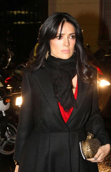 Salma Hayek donned a black coat and red gown for the Giambattista Valli show © Rex