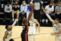 Miami Heat forward Jimmy Butler (22) shoots as Milwaukee Bucks forward Giannis Antetokounmpo (34) and center Brook Lopez (11) defend during the first half of Game 4 of an NBA basketball first-round playoff series, Saturday, May 29, 2021, in Miami. (AP Photo/Lynne Sladky)
