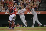 Boston Red Sox's Yoenis Cespedes, center, is greeted by Will Middlebrooks after scoring on a sacrifice fly by Xander Bogaerts as Los Angeles Angels catcher Hank Conger, foreground left, looks on during the seventh inning of a baseball game on Saturday, Aug. 9, 2014, in Anaheim, Calif. (AP Photo/Jae C. Hong)