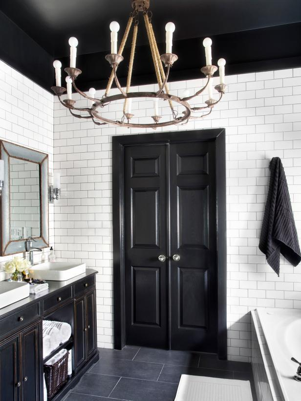 Dramatic black features like this door create a great sense of contrast with mostly white bathroom interiors.