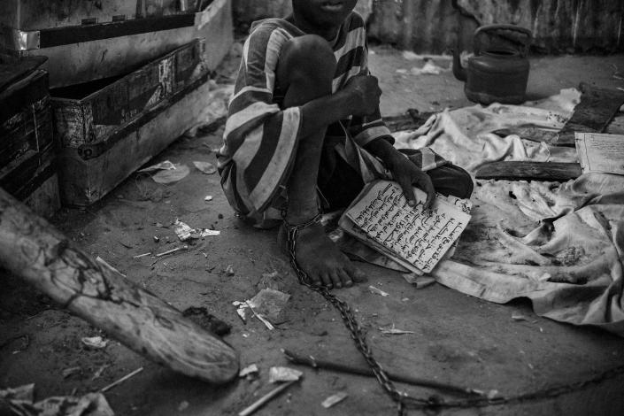 """<p>A young talibe is bound by chains in an isolation area of a daara in the city of Touba, May 27, 2015. In this daara, the youngest talibes are shackled by their ankles to stop them from trying to run away. The chain's length only allows them to use an improvised bathroom in a separate area of the daara. These children can stay like that for days, weeks, even months until they gain the trust of the marabout, or teacher. Their guardian explains, """"When I release them, I give them the freedom to beg like the rest of the talibes."""" (Photograph by Mario Cruz) </p>  <p> Talibes read the Quran inside a daara in Medina District, Dakar, Senegal, May 16, 2015. They have to memorize different parts of the Quran each day before going to the streets to beg for their guardians. (Photograph by Mario Cruz) </p>  <p> Ibrahima Ndao, marabout of a daara in Rufisque, whips a talibe after he mistakenly read an excerpt of the Quran, May 17, 2015. The talibes are subjected to physical violence when they fail to get the daily quota imposed by the marabout or if they make a mistake while reading the Quran. (Photograph by Mario Cruz) </p>  <p> Demba Fati, 14, outside the medical support room of Mason de La Gare center in St. Louis, Senegal, May 20, 2015. His marabout beat him with an iron rod after he tried to escape. Since then, he goes to the center whenever he needs medical care. (Photograph by Mario Cruz) </p>  <p> A talibe begs on a bridge in the Diamaguene area, Senegal, May 18, 2015. Children are forced to beg for an average of eight hours a day; many spend their days almost without eating and end up sleeping on the street due to accumulated fatigue. (Photograph by Mario Cruz) </p>  <p> Talibes sleep together inside a daara in Saint Louis, north of Senegal, May 21, 2015. The daara, with over 30 children, has no clean water and barely any electricity. Children sleep on the concrete floor without any protection. (Photograph by Mario Cruz) </p>  <p> Guinean military police approach a gro"""