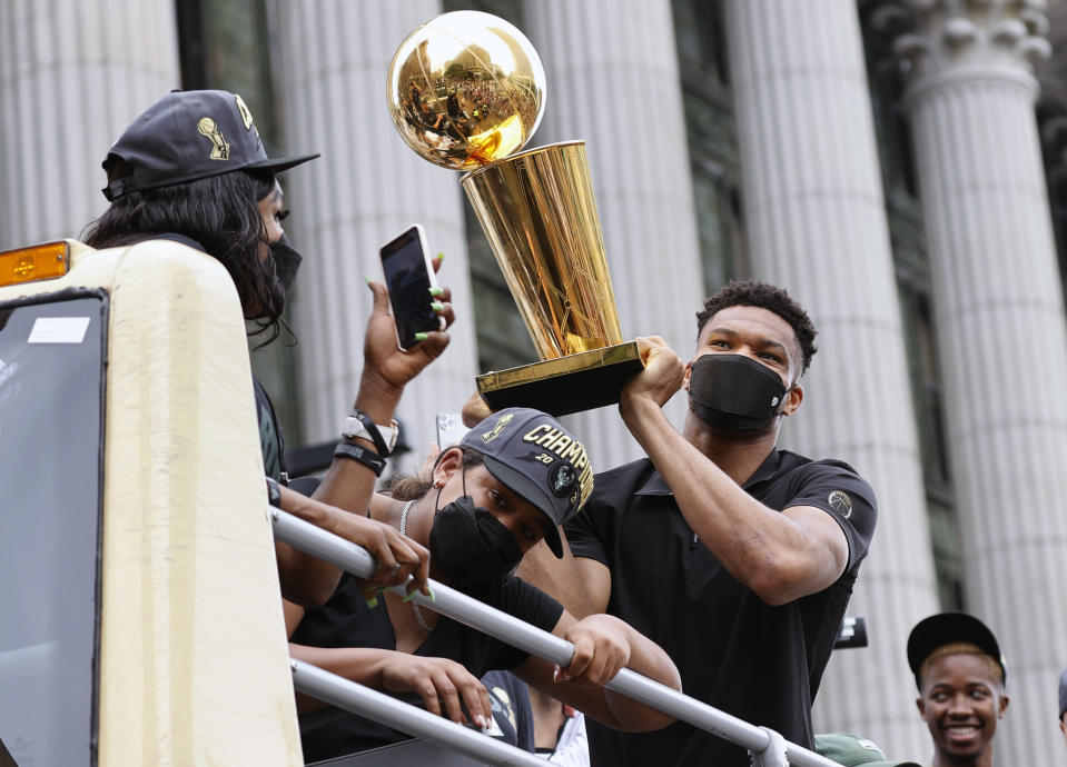 Milwaukee Bucks' Giannis Antetokounmpo, front right, holds up the NBA Championship Trophy as his mother, Veronica Antetokounmpo, left, takes a photo during a parade for the basketball team's NBA Championship win, Thursday, July 22, 2021, in Milwaukee. (AP Photo/Jeffrey Phelps)