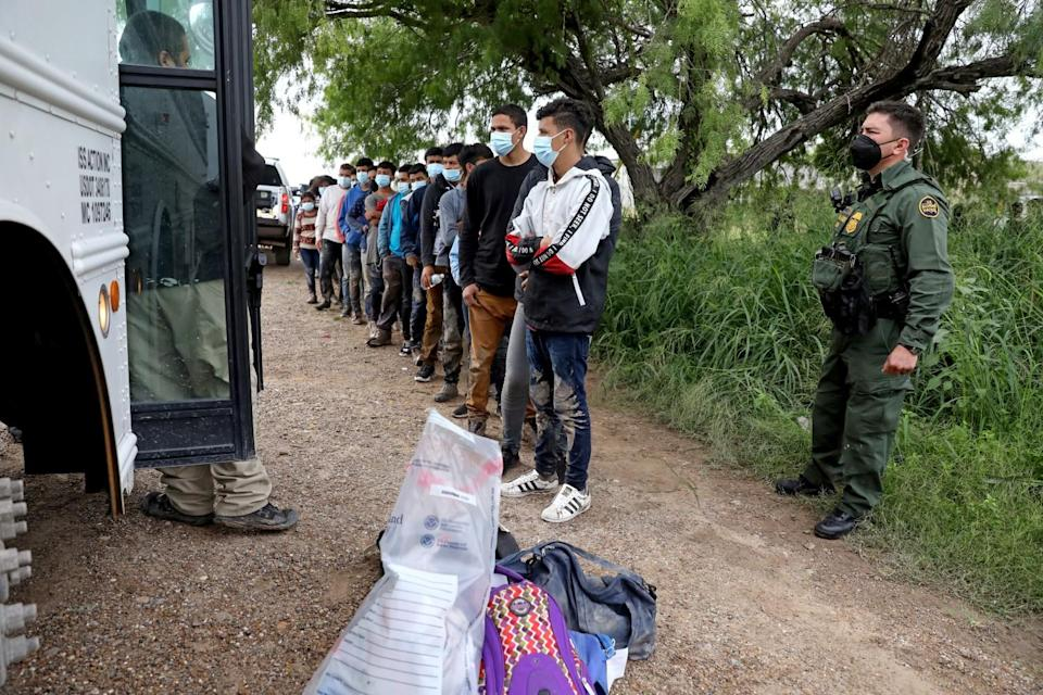 A Border Patrol agent, right, stands near a line of migrants waiting near a bus
