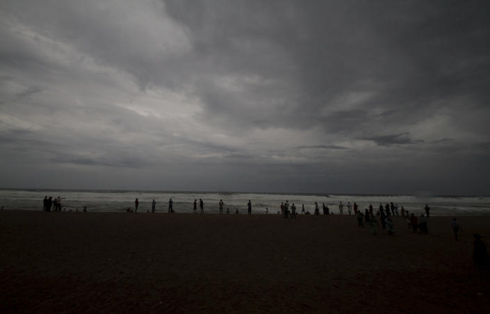 Dark clouds loom over locals standing at a beach in Puri district of eastern Odisha state, India, Thursday, May 2, 2019. Hundreds of thousands of people were evacuated along India's eastern coast on Thursday as authorities braced for a cyclone moving through the Bay of Bengal that was forecast to bring extremely severe wind and rain. (AP Photo)