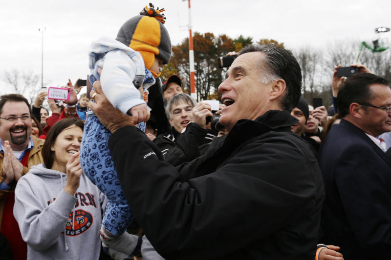 Republican presidential candidate and former Massachusetts Gov. Mitt Romney picks up Levi Vandenberg, five months, of Dover, N.H., as he greets a ropeline of supporters as he campaigns at Portsmouth International Airport, in Newington, N.H., Saturday, Nov. 3, 2012. (AP Photo/Charles Dharapak)