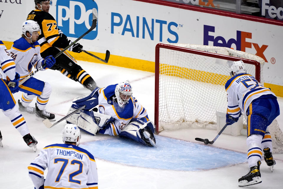 Pittsburgh Penguins center Jeff Carter (77) puts a shot behind Buffalo Sabres goaltender Michael Houser (32) for a goal during the first period of an NHL hockey game in Pittsburgh, Thursday, May 6, 2021. (AP Photo/Gene J. Puskar)