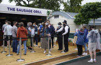 Spectators walk around the grounds during a rain delay on day one of the Wimbledon Tennis Championships in London, Monday June 28, 2021. (AP Photo/Kirsty Wigglesworth)