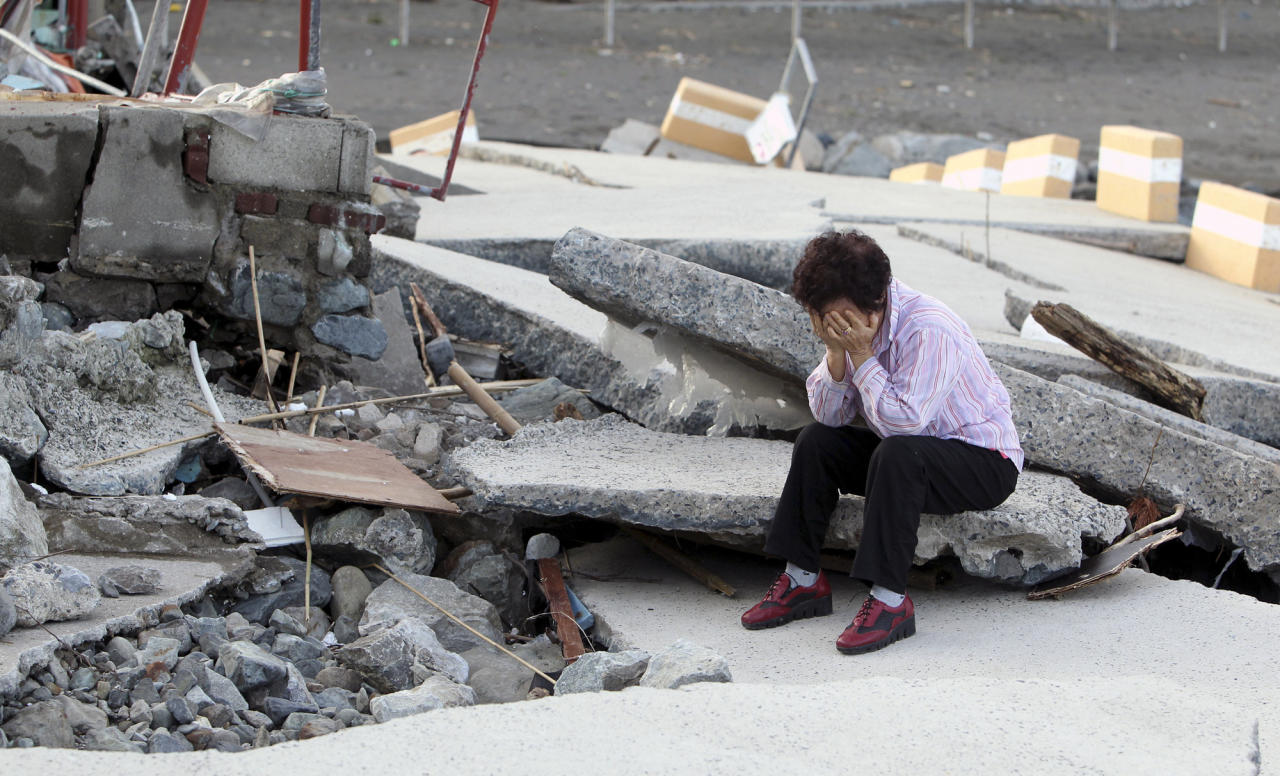 Local resident Bae Yang-soon, 70, cries on the broken road after the area was hit by Typhoon Sanba in Yeosu, south of Seoul, South Korea, Monday, Sept. 17, 2012. (AP Photo/Yonhap, Hyung Min-soo)